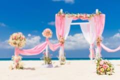 用在热带沙子海滩, outd的花装饰的婚礼曲拱 图库摄影