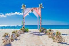 用在热带海滩, outd的花装饰的婚礼曲拱 免版税库存照片