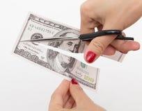 用在白色的剪刀削减的100美元 免版税库存图片