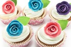 用在白色背景的玫瑰装饰的杯形蛋糕 图库摄影
