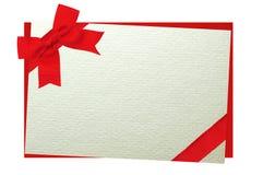 用在白色隔绝的信封的一把红色弓装饰的卡片 库存照片