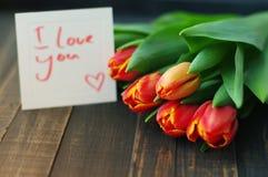 用在的红色郁金香标记我爱你黑暗的木板条 图库摄影