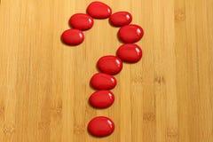 用在禅宗生活方式的红色小卵石做的问号在一个棕色竹地板 免版税库存图片