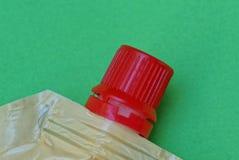 用在绿色背景的一个红色盒盖盖的一部分的一个塑料袋 库存图片