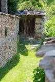 用在老石墙之间的草盖的狭窄的街道 免版税库存照片