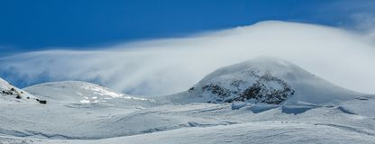 用在蓝色多云天空的雪盖的白色冬天山 修改 奥地利 Pitztaler Gletscher 图库摄影