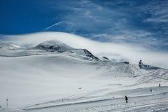用在蓝色多云天空的雪盖的白色冬天山 山滑雪者乘坐倾斜 修改 奥地利 Pitztaler Gletscher 免版税库存图片