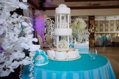 用在蓝色桌上的花装饰的甜多重婚宴喜饼 库存图片