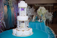 用在蓝色桌上的花装饰的甜多重婚宴喜饼 免版税图库摄影