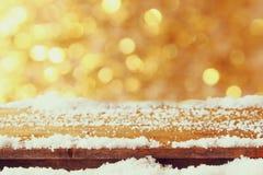用在闪烁前面的雪盖的木桌点燃 库存照片