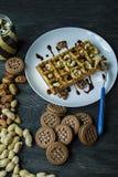 用在黑暗的木背景的巧克力盖的传统比利时华夫饼干 鲜美早餐装饰用不同的坚果, 图库摄影