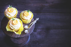 用在黑暗的木桌上的cumquat装饰的杯形蛋糕 免版税库存照片