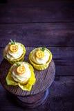 用在黑暗的木桌上的cumquat装饰的杯形蛋糕 库存图片