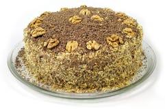 用在玻璃板的坚果装饰的自创蛋糕在白色背景 免版税库存照片