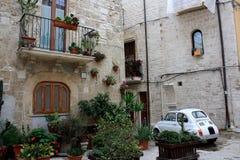 用在巴里,意大利的一个老部分的花装饰的街道 免版税库存图片