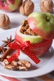 用坚果和葡萄干充塞的新鲜的红色苹果垂直 免版税库存图片
