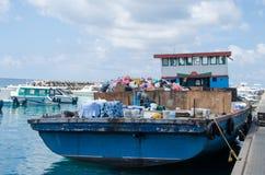 用垃圾装载的小船在码头 库存照片
