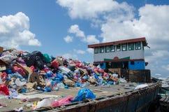 用垃圾装载的小船在码头 免版税库存图片