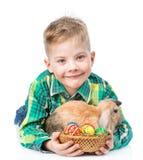用复活节彩蛋拥抱兔子的愉快的男孩 隔绝在白色b 免版税库存图片