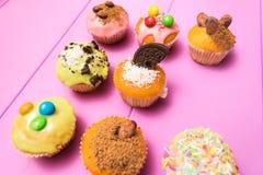用多彩多姿的结霜装饰的多个松饼、可可粉和豆、糖果和被鞭打的奶油色顶视图定了调子有选择性 库存图片