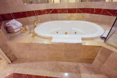 用大理石瓦片装饰的白色极可意浴缸浴缸 免版税库存图片