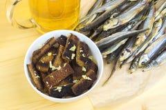 用大蒜油煎方型小面包片,一个杯子低度黄啤酒,在tabl的干鱼 免版税库存图片