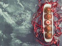 用奶油、心脏和丝带装饰的新鲜的杯形蛋糕 免版税库存照片