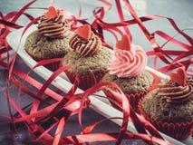 用奶油、心脏和丝带装饰的新鲜的杯形蛋糕 库存图片