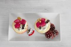 用奶油和果子充塞的苹果在白色板材 免版税图库摄影