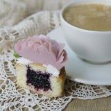 用奶油色花装饰的杯形蛋糕:在木背景的玫瑰与与咖啡的一块有花边的餐巾 杯形蛋糕片断 免版税库存照片