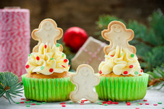 用奶油,糖五彩纸屑和ging装饰的圣诞节杯形蛋糕 库存图片