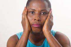 用她的手坐面颊和看照相机的哀伤的妇女 免版税库存照片