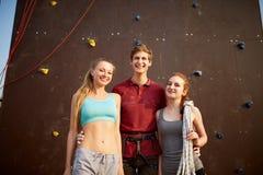 用安全设备微笑和看照相机的小组三个攀岩运动员对人为上升的墙壁 库存照片