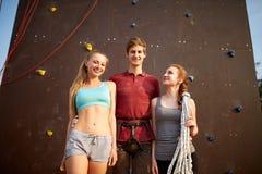 用安全设备微笑和看照相机的小组三个攀岩运动员对人为上升的墙壁 免版税库存照片