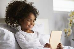 用完数字式片剂的微笑的女孩在床,关闭 库存照片