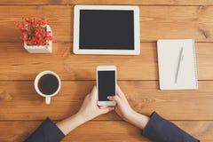 用完电话的女性在工作场所,顶视图,关闭 免版税库存图片