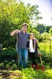 用小锄头莴苣庭院的人和女儿供住宿热的夏日 免版税库存照片