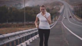 用尽镇的一双白色T恤杉和明亮的运动鞋的一位年轻运动员 健康生活方式 在背景  股票视频