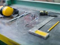 用工具加工在一张灰色背景桌上的木匠特写镜头 免版税库存照片
