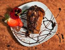 用巧克力奶油,新鲜的草莓、蝴蝶花和可可粉装饰的那不勒斯的点心 免版税图库摄影