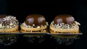 用巧克力釉盖的三个法国微型圆的奶油甜点酥皮点心点心全景  影视素材