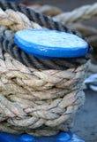 用巩固报道的蓝色小船停泊岗位系住 免版税库存照片