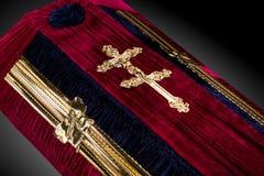 用布料盖的闭合的红色天鹅绒棺材隔绝在灰色背景 与金教会十字架的棺材特写镜头 图库摄影