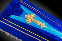 用布料盖的闭合的蓝色棺材隔绝在灰色背景 与金教会十字架的棺材特写镜头 免版税库存照片