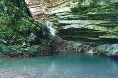 用常春藤和青苔盖的岩石与流动一点瀑布 免版税库存照片
