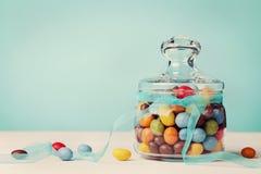用弓丝带装饰的五颜六色的糖果瓶子反对蓝色背景 库存照片