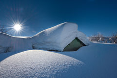用很多雪盖的小屋在大雪以后 免版税库存图片