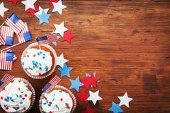 用愉快的美国独立日7月4日背景的美国国旗装饰的杯形蛋糕 假日台式视图 免版税库存图片
