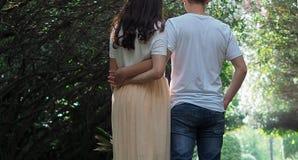 用手一起走手在公园,背面图的年轻夫妇 图库摄影