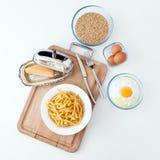 用手做的意大利tagliatelle面团 家做意粉 烹调意大利语的食品成分 面粉,鸡蛋,乳酪, -烹调在木sla的成份 免版税图库摄影